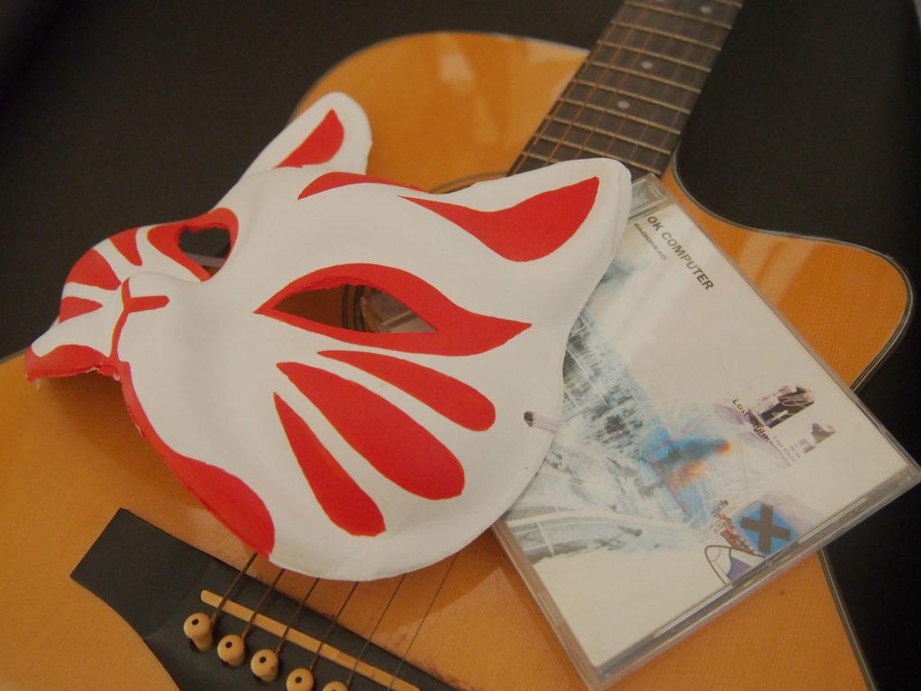 狐のお面とギターとレディオヘッドのアルバム(トム・ヨークと日本のつながりイメージ))