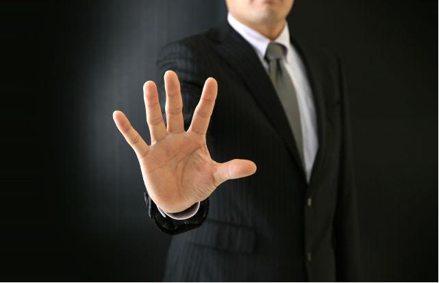 手で制するビジネスマン(反対の声イメージ)